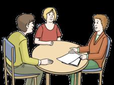 Zwei Männer sitzen an einem Tisch. Ein Mann redet und erklärt dem anderen etwas.