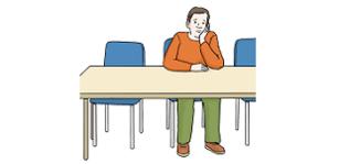 Das Bild zeigt einen Mann. Er sitzt alleine an einem Tisch.