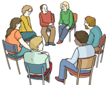 Viele Jugendliche sitzen in einem Kreis. Sie reden miteinander.