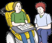 Das Bild zeigt einen Rollstuhlfahrer. Der Rollstuhlfahrer hat ein Buch in der Hand. Ein Mann erklärt ihm etwas.